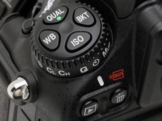 Točkić sa četiri tastera (QUAL, WB, BKT, ISO) i prstenom na kome su vertikalno naznačene preostale opcije levog bloka – pojedinačno i kontinuirano okidanje, Self‑timer, Quiet režim i Mirror lock‑up