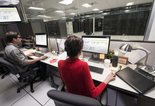 Man and Woman Seated at Desk Using Optiplex 9020 AIO and Latitud