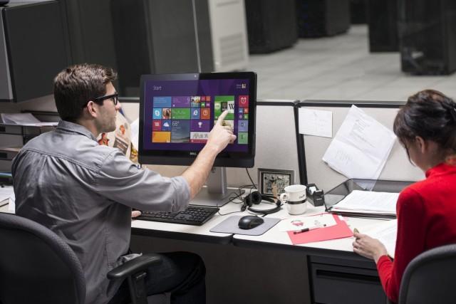 Man and Woman Seated at Desk Using Optiplex 9030 AIO Desktop Com