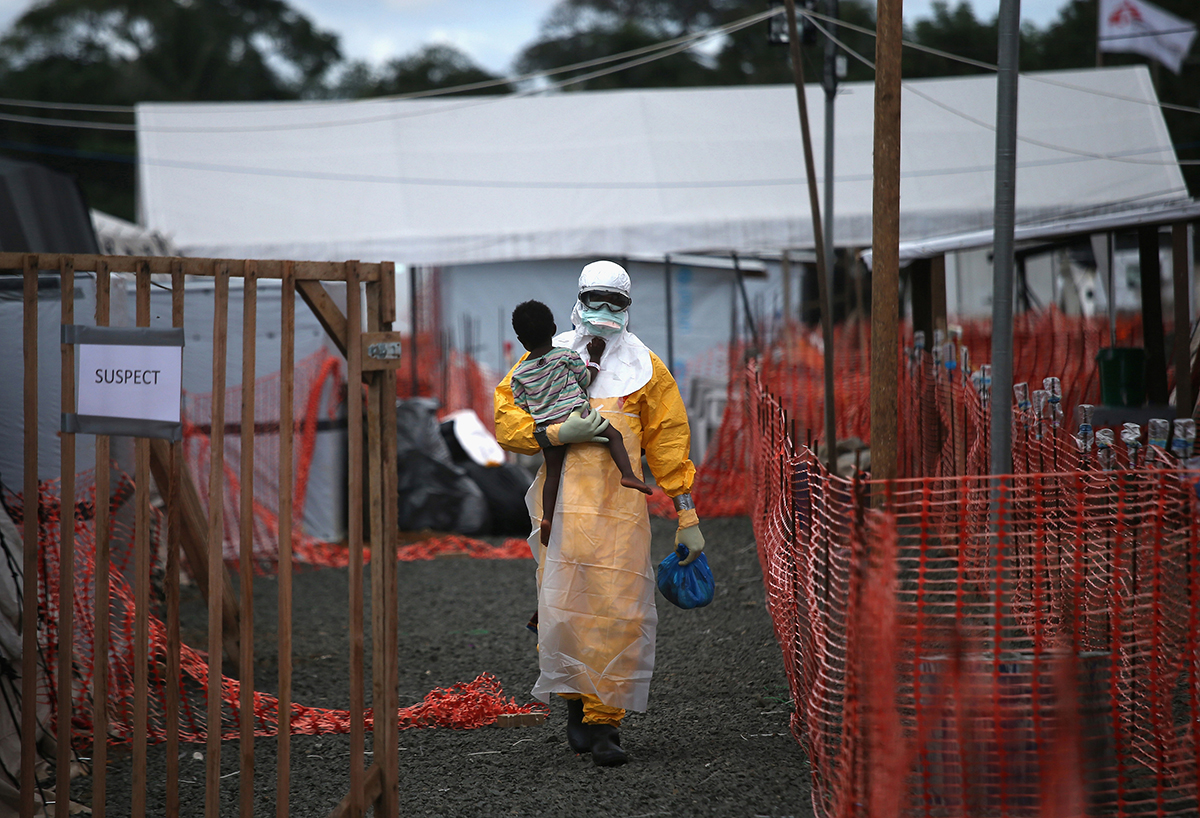 A Doctors Without Borders (MSF), health worker in protective clothing carries a child suspected of having Ebola at the MSF treatment center on October 5, 2014 in Paynesville, Liberia. The girl and her mother, both showing symptoms of the virus, survived and were released about a week later.