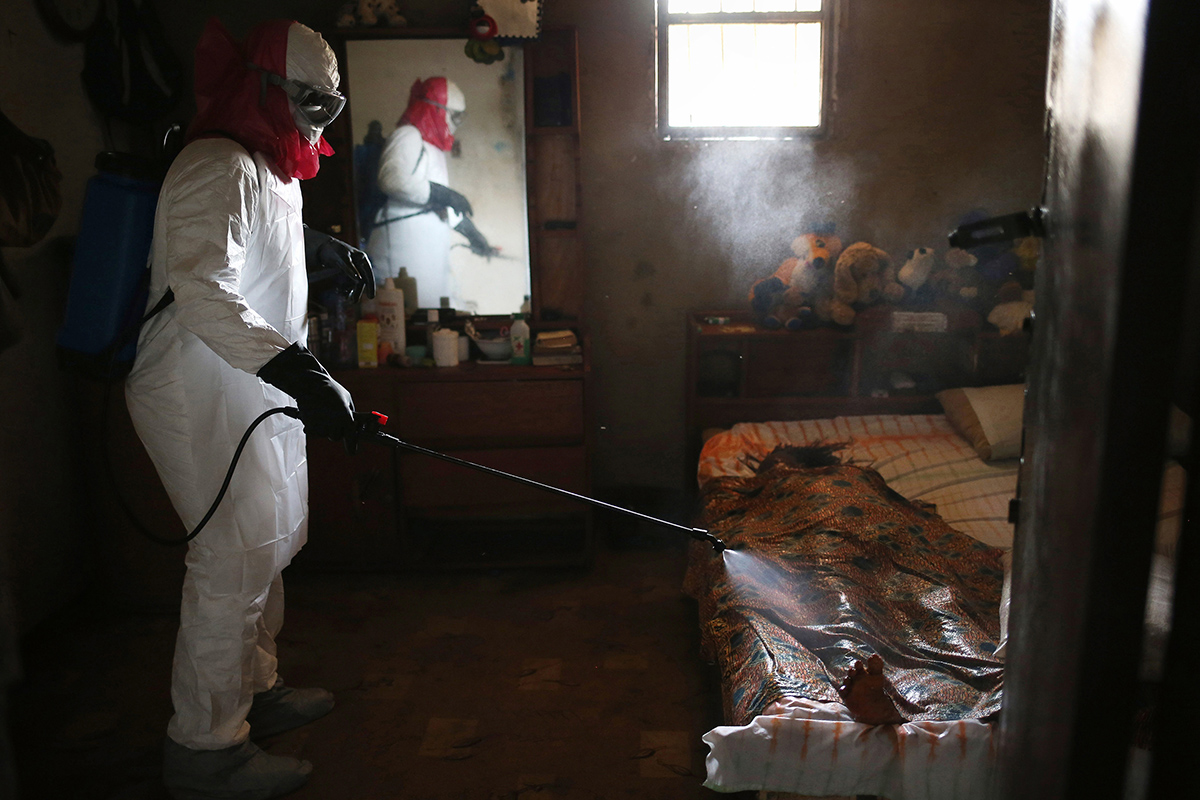 A burial team from the Liberian Red Cross sprays disinfectant over the body of a woman suspected of dying of the Ebola virus on August 14, 2014 in Monrovia, Liberia. Teams retrieved dozens of bodies from all over the capital of Monrovia, where the Ebola virus spread quickly last summer.